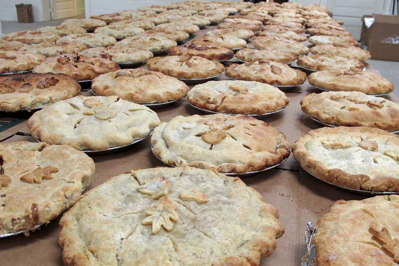 A very large table covered with baked apple pies