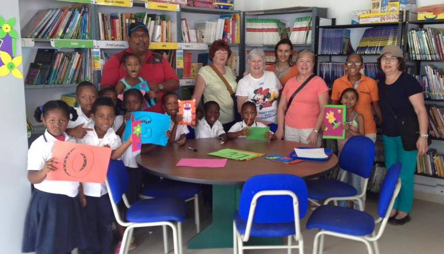 Columbia project volunteers with children in the library